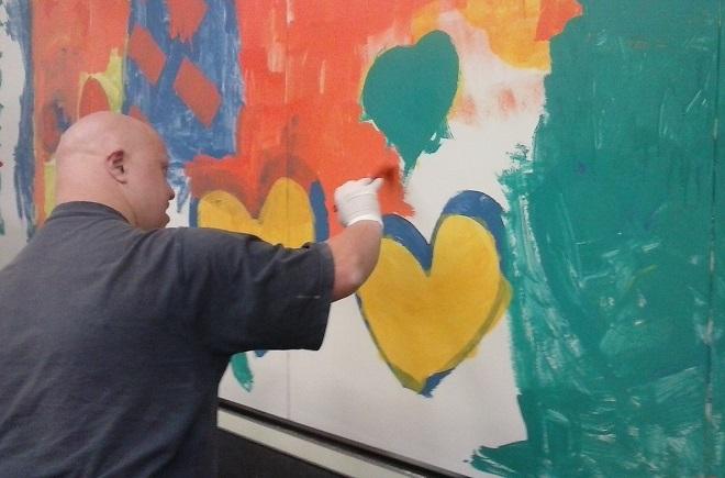 Un artista de Grupo AMÁS pintando El Mural de la Inclusión. Foto: Grupo AMÁS.