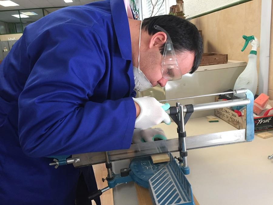 David Carmona cortando las fichas de madera del juego. Foto: Grupo AMÁS.