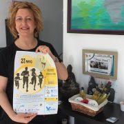 """Celia de la Cruz, propietaria de """"Duendes Peluqueros"""" muestra el cartel de la X Carrera por la Inclusión. Foto: Grupo AMÁS"""